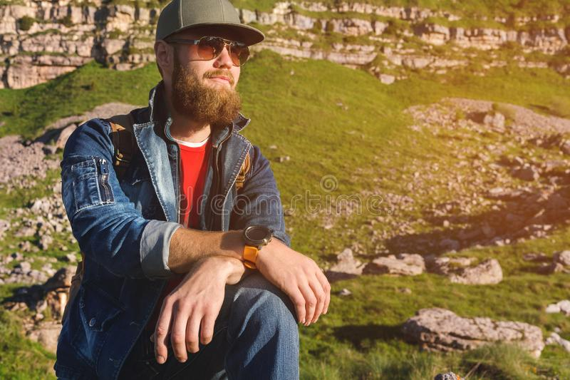 Close-up of a bearded man in jeans clothes in sunglasses and a cap with a backpack sitting at the foot of the epic rocks royalty free stock images