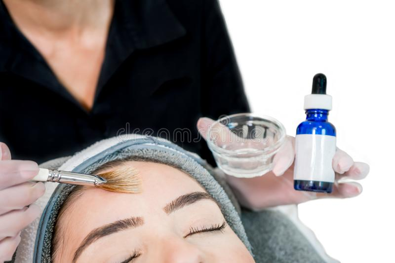 Close up of beautician cosmetologist applying chemical peel treatment on patient in a beauty spa, for skin rejuvenation, royalty free stock photo