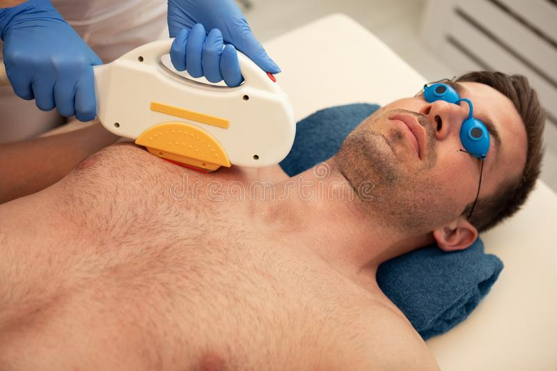 Laser epilation treatment to man chest stock images
