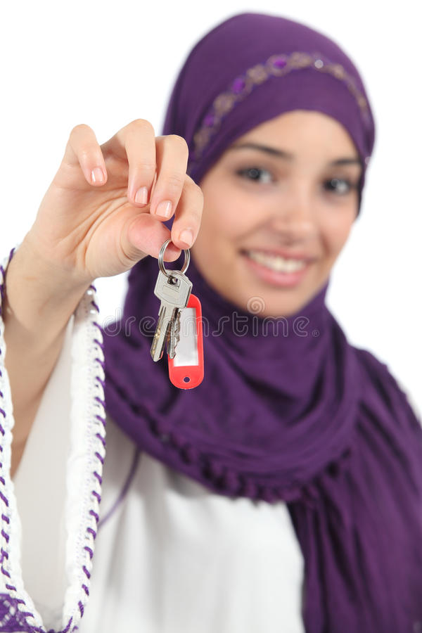 Close up of a beautiful arab woman holding a home keys. Isolated on a white background stock images