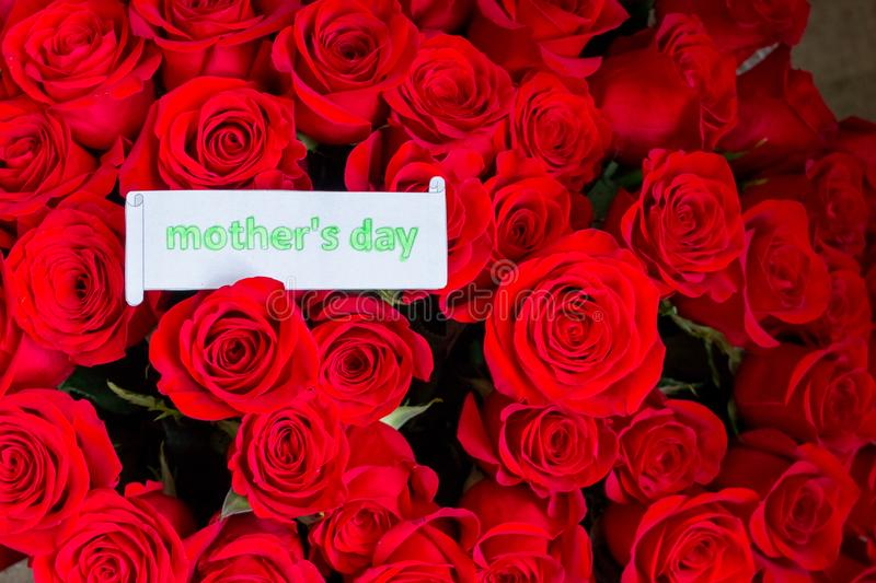 Close up of a beautiful bouquet of red roses with a happy mothers day card. Mother`s Day concept.spring holidays and stock image