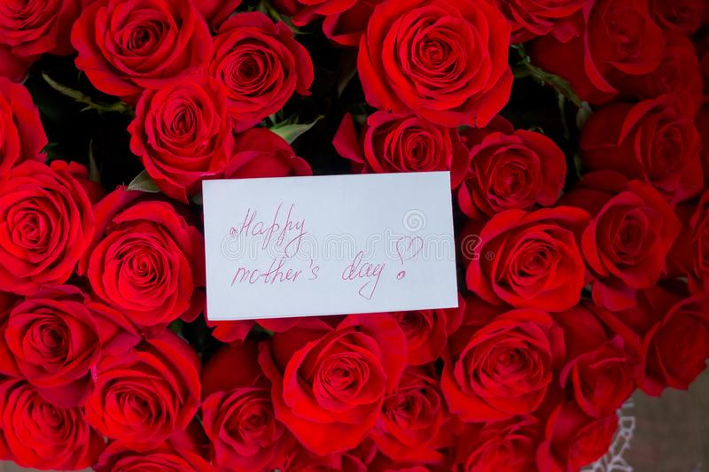 Close up of a beautiful bouquet of red roses with a happy mothers day card. Mother`s Day concept.spring holidays and royalty free stock image