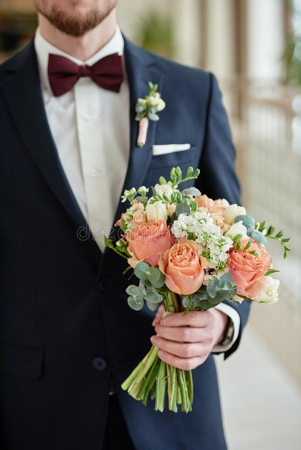 Close up of beautiful bridal bouquet of coral roses and greenery in groom& x27;s hand indoors, copy space. Flower, bride, love, trendy, white, woman, marriage stock photos
