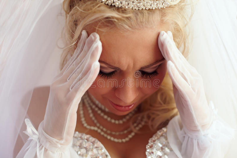Close-up of beautiful bride frown on troubles. Close-up portrait of beautiful bride frown on the troubles and pain. white background stock images