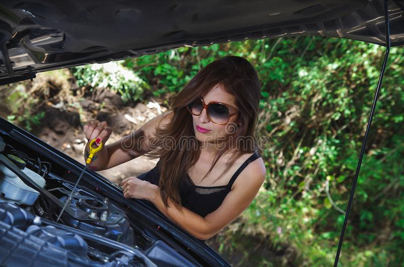 Close up of beautiful caucasian woman, checking the oil by herself and wearing sunglases, black t-shirt and jeans royalty free stock photography