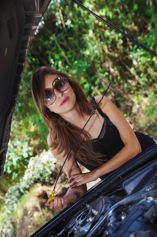 Close up of beautiful caucasian woman, checking the oil by herself and wearing sunglases, black t-shirt and jeans stock photos