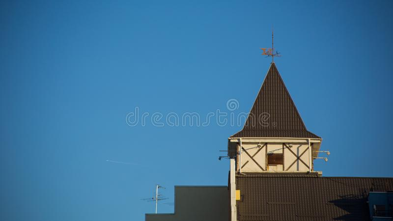 Beautiful elegant brown tower located on roof of house against blue boundless sky. Close-up beautiful elegant brown tower located on roof of house against blue stock images