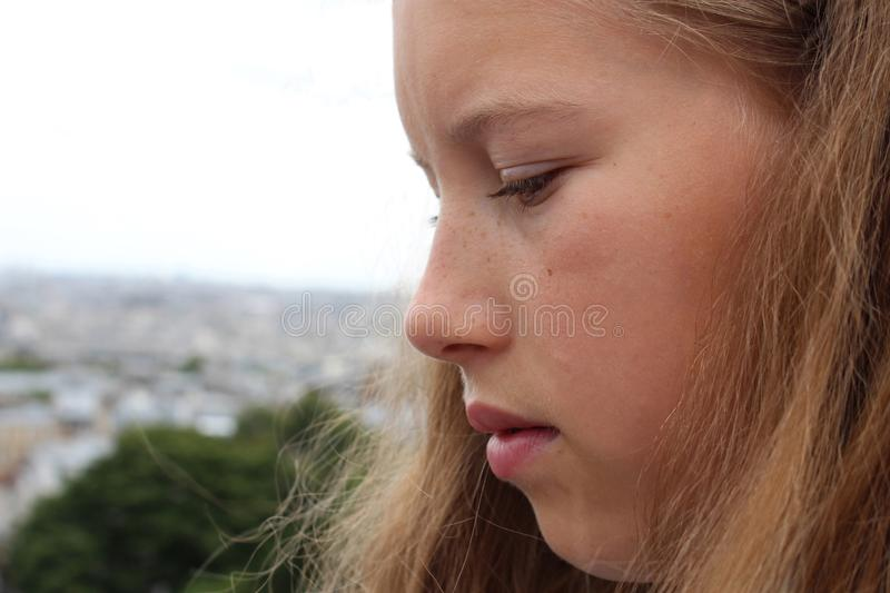 Close-up beautiful face of a contemplative girl looking down.. Close-up beautiful face of a blond contemplative girl looking down. Eyes with long eyelashes stock images