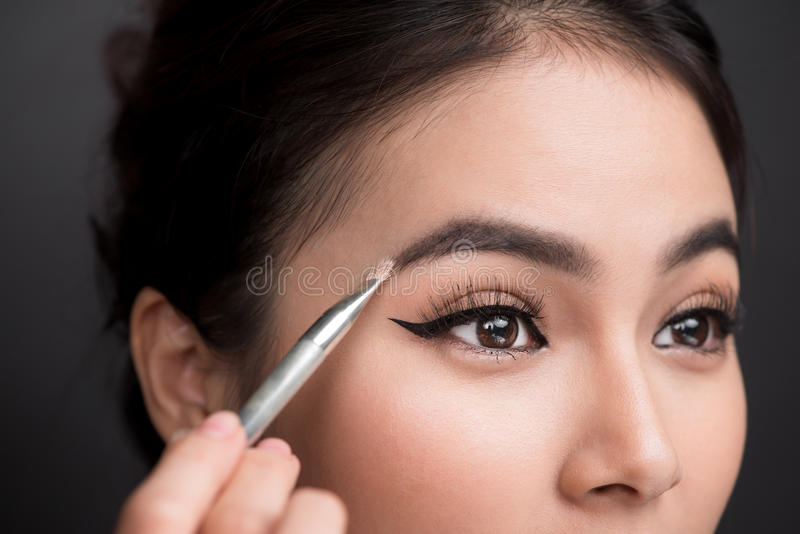 Close up of beautiful face of young asian woman getting make-up. The artist is applying eyeshadow on her eyebrow with brush stock photography