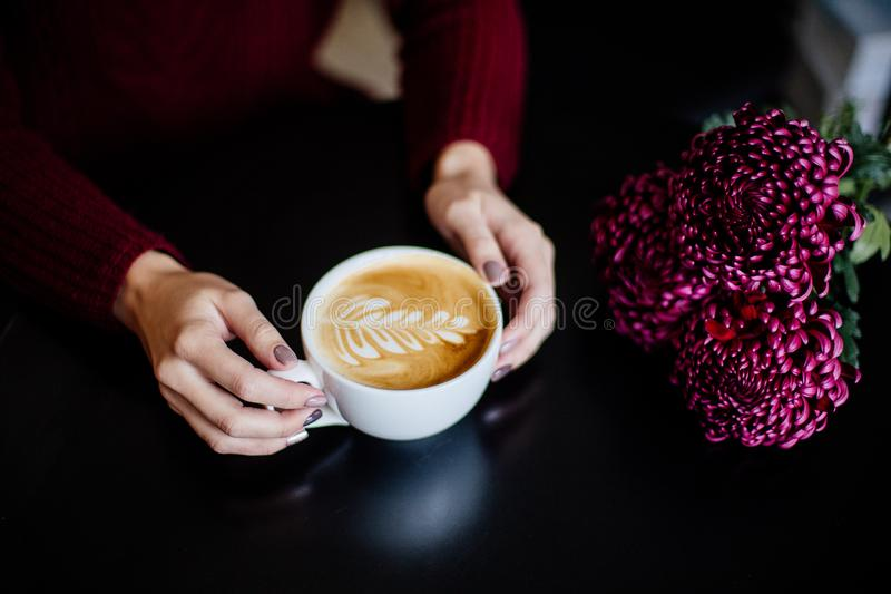 Cup of cappuccino in hand. Close up of beautiful female hand holding big white cup of cappuccino coffee stock image
