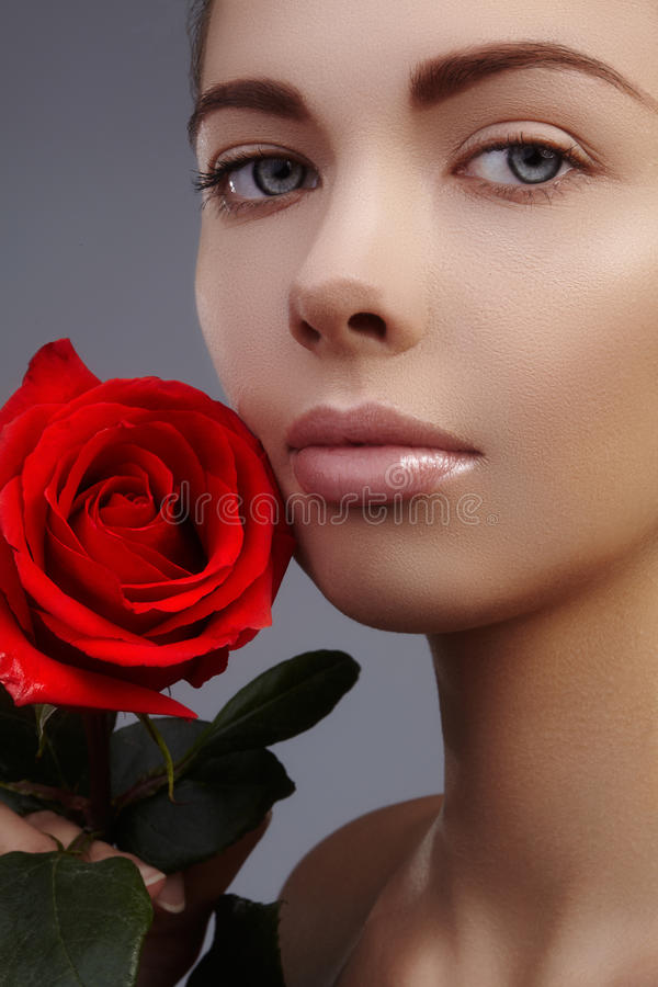 Close-up beautiful female lips with bright lipgloss makeup. Perfect clean skin, red lip make-up stock photography