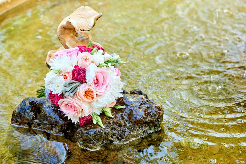 Close up of beautiful fresh wedding bouquet of pink and white roses on stone in water  near fish in fountain, free space. Wedding. Details outdoor with copy royalty free stock photo