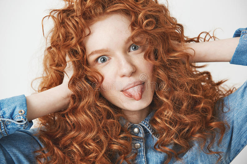 close up of beautiful ginger girl touching hair smiling showing