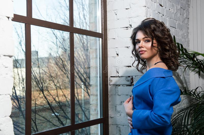 Close up. A beautiful girl in a blue jacket is standing near the panoramic window, flirty-bare her shoulder. Outside the window is royalty free stock photography