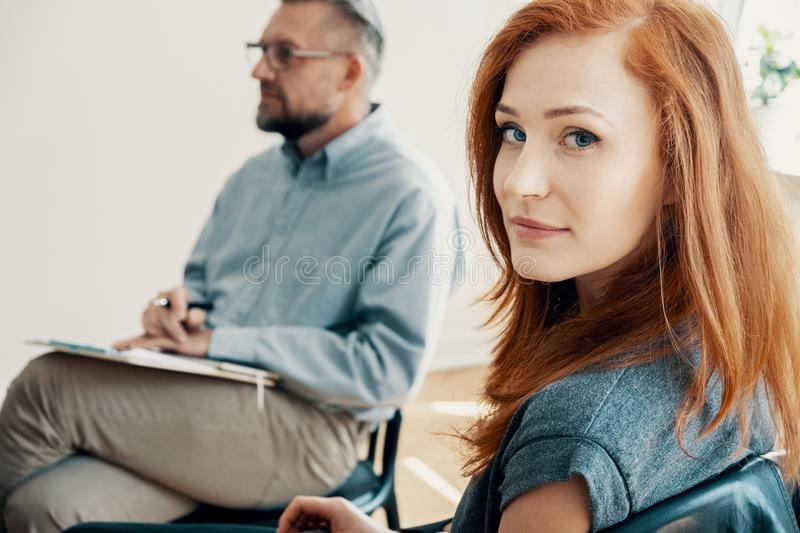 Close-up of a beautiful girl looking at the camera with a therapist in the background stock image