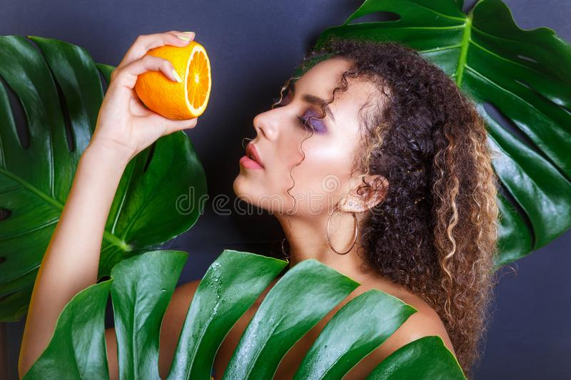 Close-up of beautiful girl posing in tropical forest. Portrait of beautiful African American woman with tropical fruits stock image