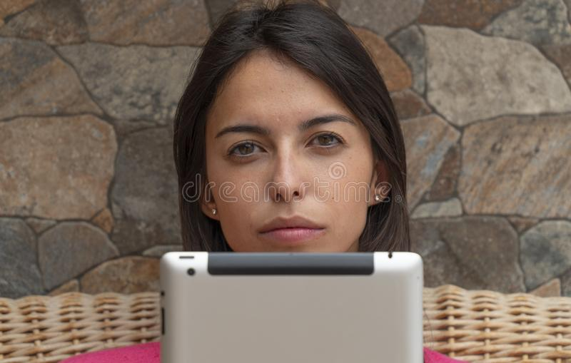 Close-up of beautiful girl sitting with the tablet. Adolescence holding a notebook hiding after the screen. Serious Teenager royalty free stock image
