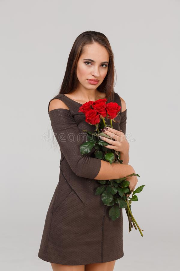 Young beautiful girl with bouquet of red roses on a grey background. 8 March concept. royalty free stock photo