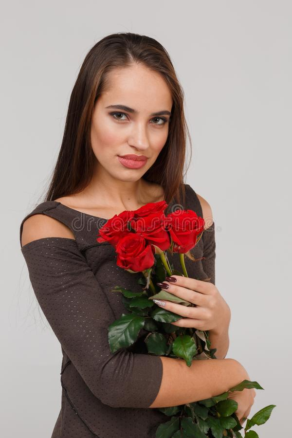 Young beautiful girl with bouquet of red roses on a grey background. 8 March concept. royalty free stock image