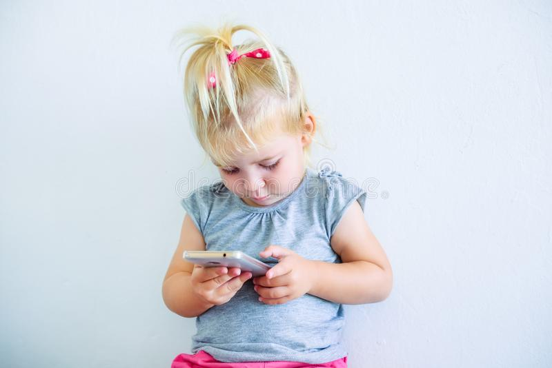 Close up Beautiful little baby girl holding and playing with smart phone on the white wall background. Children and technology con. Cept. Selective focus. Space royalty free stock images