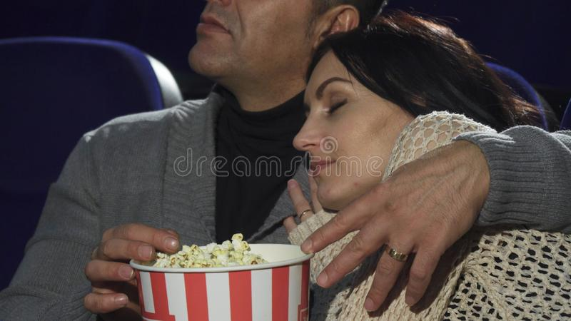 Mature woman sleeping on the shoulder of her husband at the cinema royalty free stock image