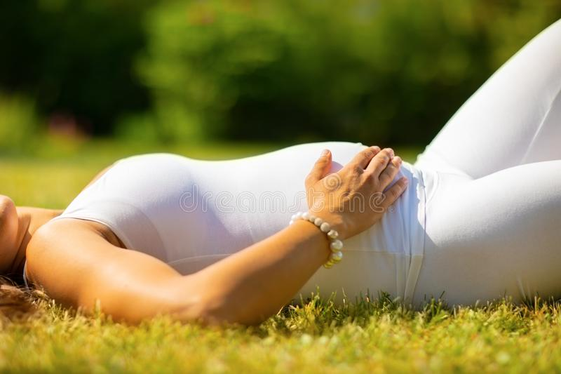 Close-up of beautiful pregnant woman in white clothes laying on grass stock photography