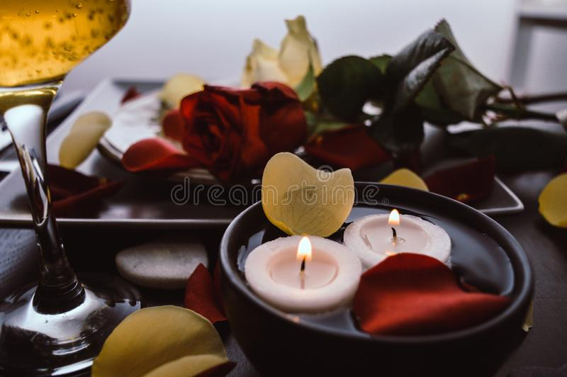 Close-up of a beautiful romantic dinner with champagne glass bubbles, flowers petals, roses, candles. Valentine`s day stock photos