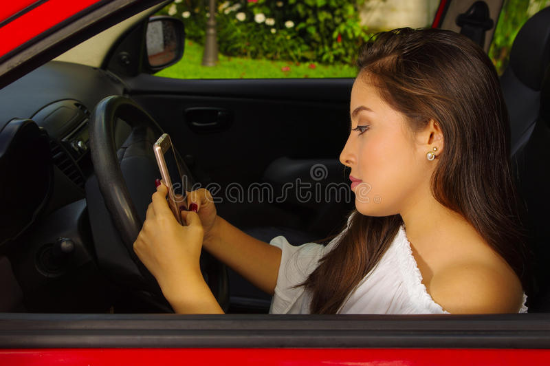 Close up of a beautiful young woman in red car texting from her cellphone stock image