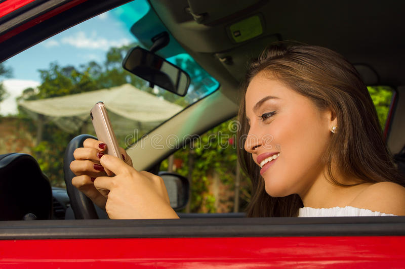 Close up of a beautiful young woman in red car using her cellphone and smiling.  royalty free stock photos
