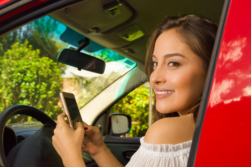 Close up of a beautiful young woman in red car using her cellphone and smiling.  royalty free stock image
