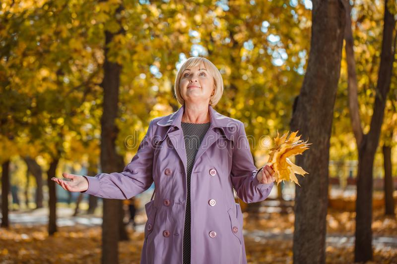 An attractive middle-aged woman walking in an autumn park on a blurred background. royalty free stock photography
