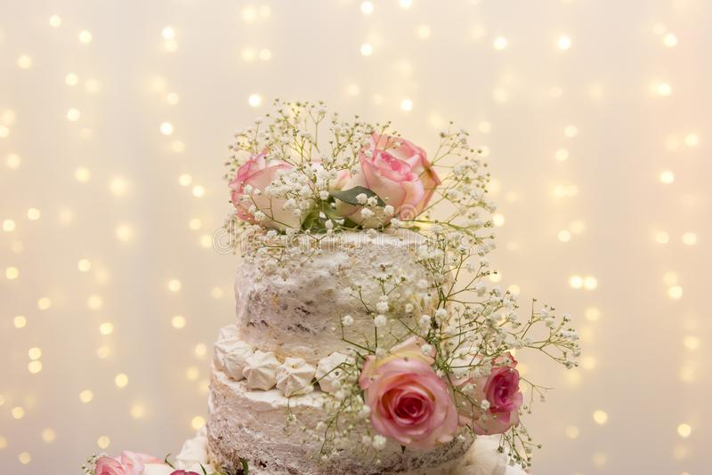 Close up of beautiful white tree tier cake with fresh flowers with fairly light and lanterns glowing in the background. Selective focus. Copy space royalty free stock photography