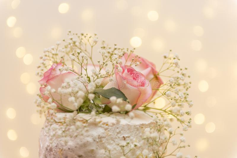 Close up of beautiful white tree tier cake with fresh flowers with fairly light and lanterns glowing in the background. Selective focus. Copy space royalty free stock photo