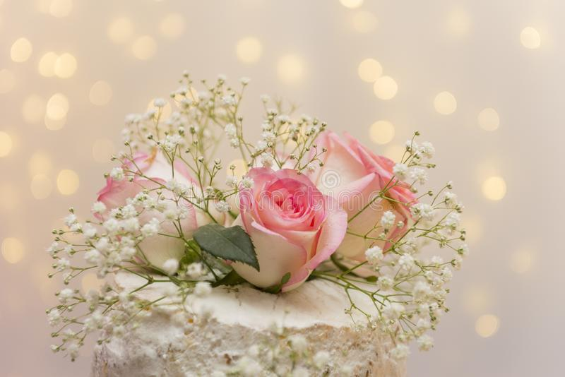 Close up of beautiful white tree tier cake with fresh flowers with fairly light and lanterns glowing in the background. Selective focus. Copy space stock photo