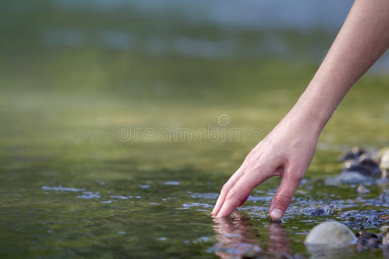 Close-up of beautiful white woman hand tenderly touching, scooping clean fresh sweet water on blurred green copy-space background stock images