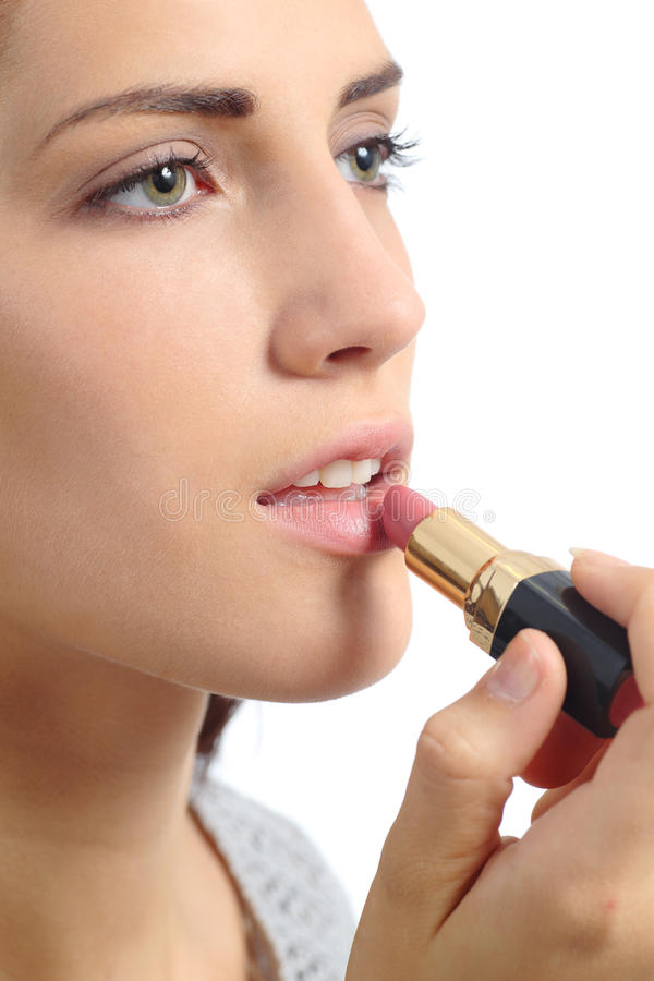 Close up of a beautiful woman applying a lipstick on lips royalty free stock photos
