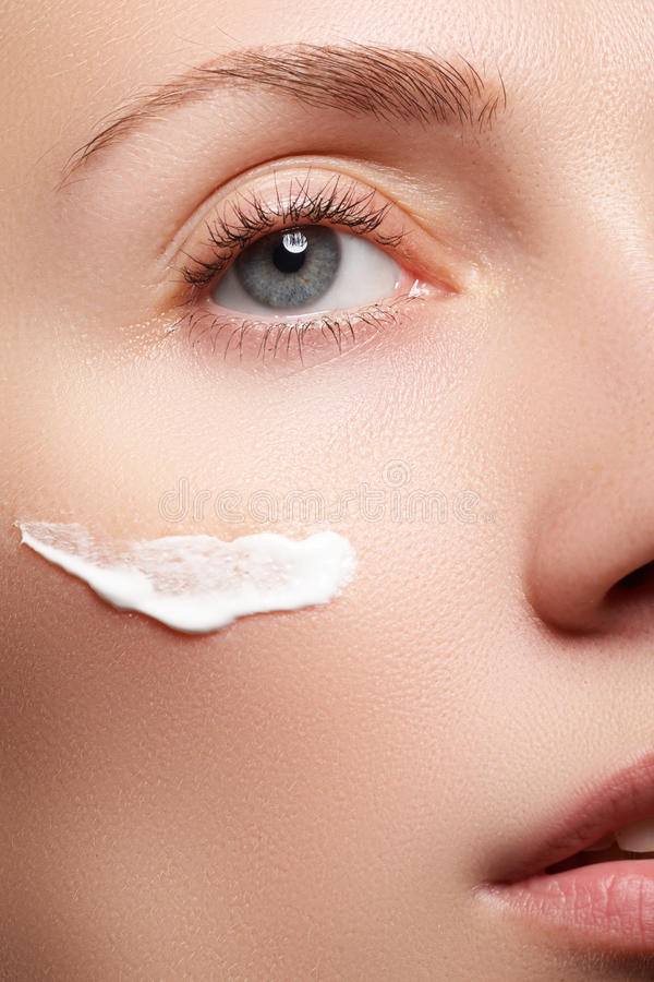 Close-up of beautiful woman eye. Woman applying moisturizing cream. Beauty concept royalty free stock photography