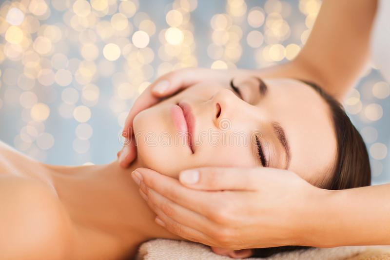 Close up of beautiful woman having face massage. Wellness, spa and beauty concept - close up of beautiful woman having face massage over holidays lights stock image