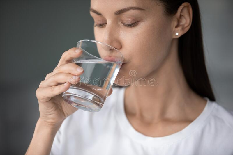 Close up beautiful woman with perfect healthy skin drinking water stock photography