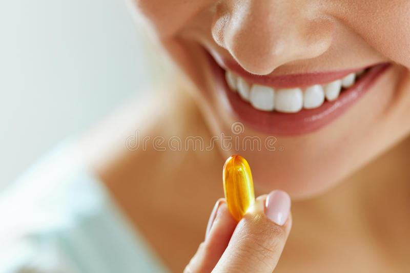 Close Up Of Beautiful Woman Taking Fish Oil Capsule In Mouth royalty free stock image