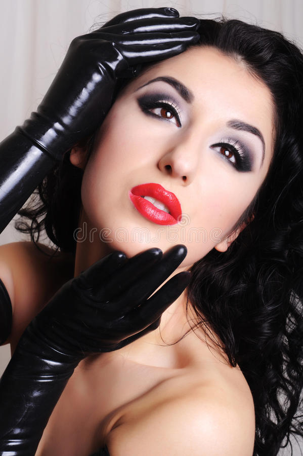 Close up of a beautiful woman wearing black latex gloves royalty free stock images
