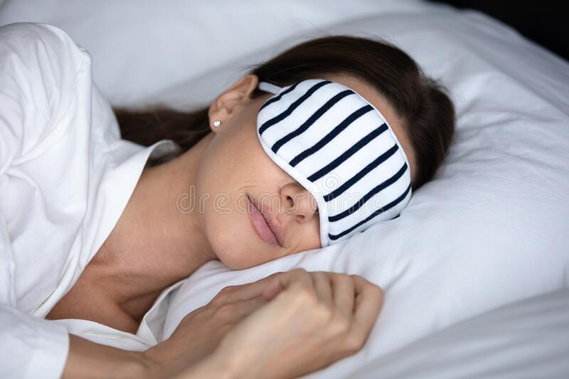 Close up beautiful woman wearing sleeping mask lying in bed stock photo