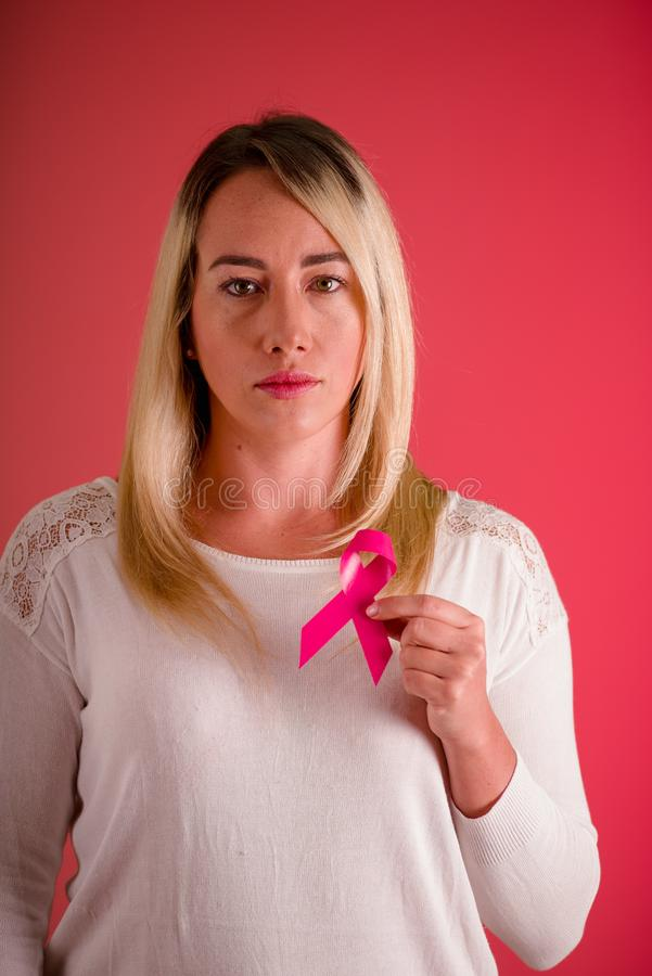Close up of a beautiful woman wearing a white blouse and holding a pink breast cancer awareness ribbon, cancer concept stock photography