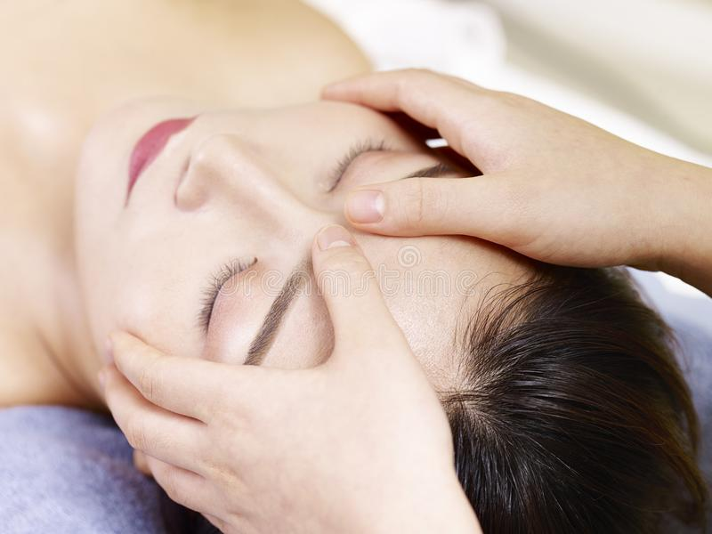 Young asian woman receiving face massage in spa salon stock photography