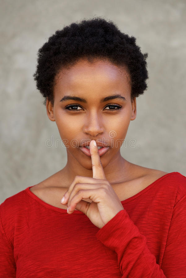 Close up beautiful young black woman with finger over lips stock photos