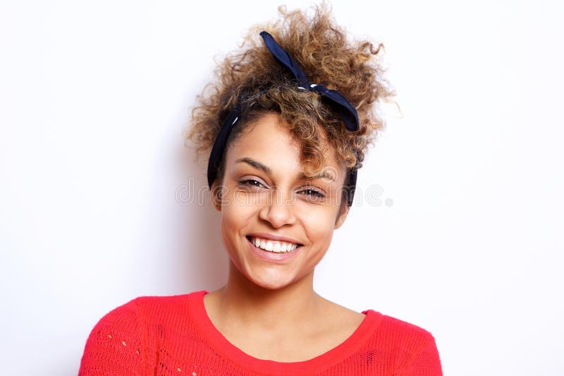 Close up beautiful young black woman with hair bandana smiling against white wall. Close up portrait of beautiful young black woman with hair bandana smiling stock images