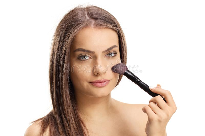 Close up of a beautiful young girl applying make up with a brush stock photos
