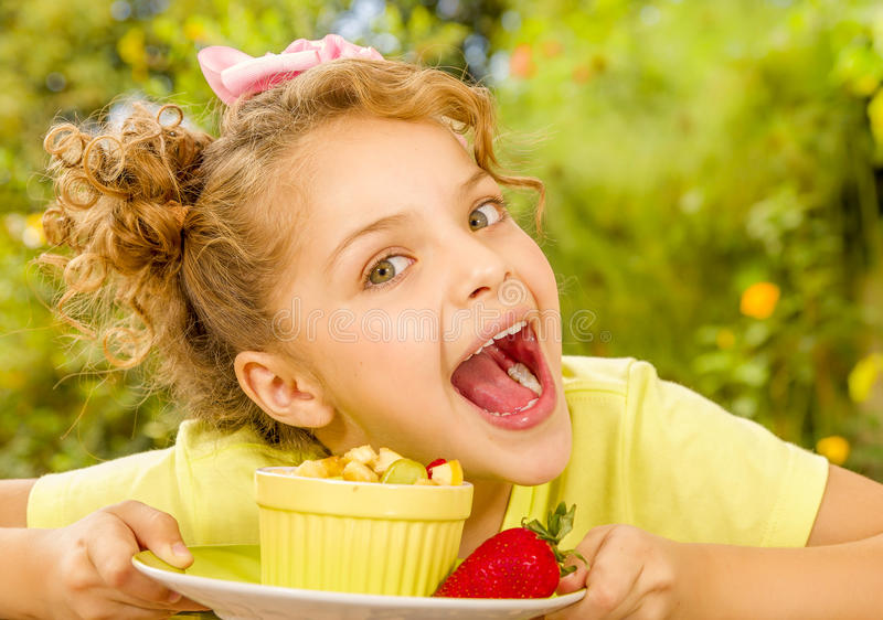 Close up of a beautiful young girl wearing a yellow t-shirt, preparing to eat a healthy fruit salad in a garden stock photos