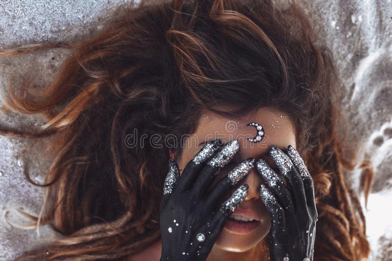 Close up of beautiful young woman cover eyes with hands painted black. night and moon concept stock photos