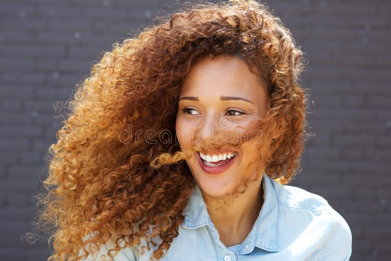 Close up beautiful young woman with curly hair smiling and looking away stock photography